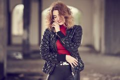 Smiling fashionable red-haired girl with flowing hair in black leather pants, red sweater and black jacket posing in a large room. Shallow depth of field royalty free stock images