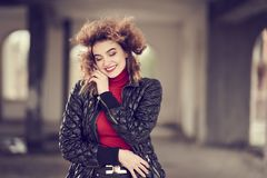 Smiling fashionable red-haired girl with flowing hair in black leather pants, red sweater and black jacket posing in a large room. Shallow depth of field stock photos