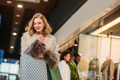 smiling fashionable young woman in fur coat holding shopping bags while walking stock images
