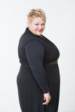 Smiling fat woman in black dress. Light background Royalty Free Stock Images