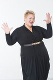 Smiling fat woman in black dress. Light background Stock Images