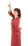 Smiling fat young woman in red dress pointing up Royalty Free Stock Images