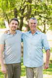 Smiling father with adult son at park Royalty Free Stock Photo