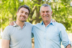 Smiling father with adult son at park Stock Photos