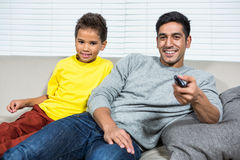 Smiling father ans son watching tv on the sofa Royalty Free Stock Photos