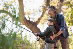 Smiling father assisting son while fishing in forest. Smiling father assisting son while fishing on sunny day in forest royalty free stock photos