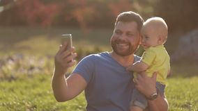 Smiling father and baby son making selfie in park stock video