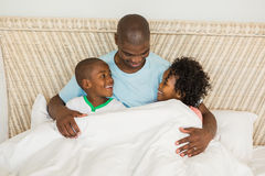 Smiling father in bed with children Stock Image