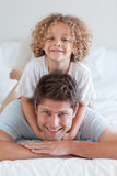 Smiling father and child lying on bed Stock Images