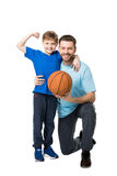 Smiling father and child ready to play basketball. Boy showing his biceps Stock Image
