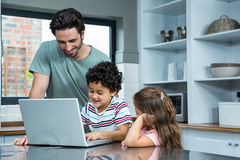 Smiling father and children using laptop Stock Photos
