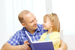 Smiling father and daughter with book at home royalty free stock photography