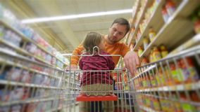 Smiling father and daughter chooses products in the supermarket, man buys drinks in store stock footage
