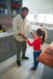 Father and daughter dancing together in kitchen. Smiling father and daughter dancing together in kitchen Stock Images