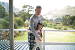 Smiling father and daughter embracing each other in balcony. Portrait of smiling father and daughter embracing each other in balcony Royalty Free Stock Photo