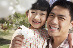 Smiling father and daughter enjoying the cherry blossoms on the tree in the park in springtime Royalty Free Stock Photography
