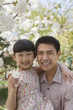 Smiling father and daughter enjoying the cherry blossoms on the tree in the park in springtime, portrait Royalty Free Stock Images