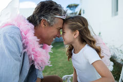 Smiling father and daughter in fairy costume standing face to face Stock Image