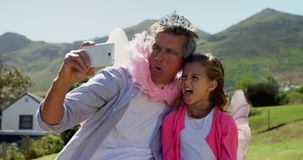Smiling father and daughter in fairy costume taking selfie with mobile phone 4k. Smiling father and daughter in fairy costume taking selfie with mobile phone at stock video