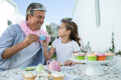 Smiling father and daughter in fairy costume toasting cup of tea Stock Photo