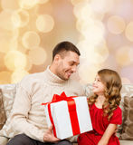 Smiling father and daughter with gift box. Family, christmas, holidays and people concept -smiling father and daughter with gift box over beige lights background Stock Image