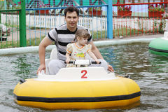 Smiling father and daughter go boating in park Royalty Free Stock Photo