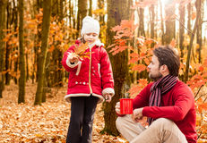 Smiling father and daughter having fun outdoor in an autumn park Stock Photos