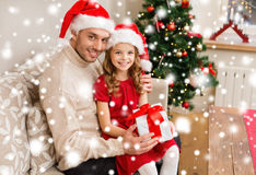 Smiling father and daughter holding gift box Stock Photo