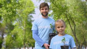 Smiling father and daughter holding green plant saplings, reforestation fund