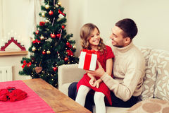 Smiling father and daughter looking at each other. Christmas, x-mas, winter, happiness and people concept - smiling father and daughter holding gift box and Royalty Free Stock Images