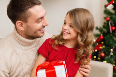 Smiling father and daughter looking at each other. Family, christmas, x-mas, winter, happiness and people concept - smiling father and daughter holding gift box Royalty Free Stock Image