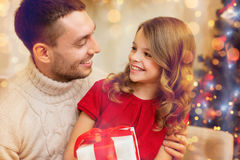 Smiling father and daughter looking at each other. Family, christmas, x-mas, winter, happiness and people concept - smiling father and daughter holding gift box Royalty Free Stock Photo