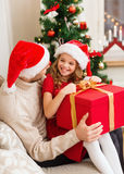 Smiling father and daughter opening gift box Stock Photos
