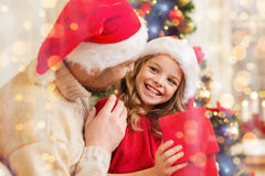 Smiling father and daughter opening gift box Stock Photography