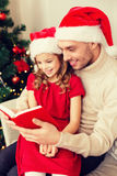 Smiling father and daughter reading book Stock Photo