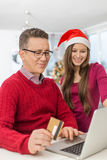 Smiling father and daughter shopping online at home during Christmas royalty free stock photography