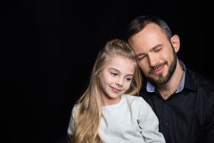 Smiling father and daughter. Sitting together on black Stock Image