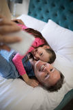 Smiling father and daughter taking selfie with mobile phone on bed Stock Image