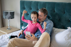 Smiling father and daughter taking selfie with mobile phone on bed Stock Photography