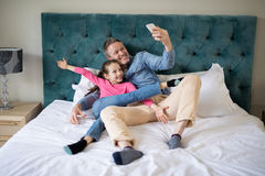 Smiling father and daughter taking selfie with mobile phone on bed Royalty Free Stock Photography