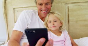 Smiling father and daughter using mobile phone on bed 4k. Smiling father and daughter using mobile phone on bed in bedroom 4k stock video