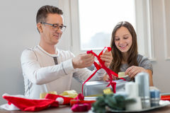 Smiling father and daughter wrapping Christmas present at home stock photos