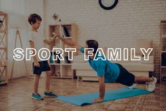 Smiling Father Is Doing Push Ups. Sport Family. Healthy Lifestyle. Active Holiday. Exercises Clothes. Getting Better. Working Out At Home. Gym Carpet. Repeat Royalty Free Stock Photography