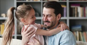 Smiling father embracing small cheerful child daughter at home.