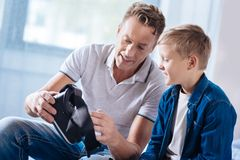 Smiling father examining VR headset working principles. Clear explanation. Cheerful pleasant men sitting next to his son, holding a VR headset and explaining the Royalty Free Stock Photography