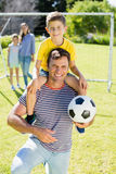 Smiling father with football carrying his son on shoulder at the park Stock Image