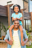 Smiling father giving daughter a piggyback Stock Photography