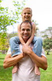 Smiling father giving his daughter piggy-back ride Royalty Free Stock Images