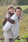 Smiling father giving son piggyback ride outdoors.  Stock Photo