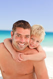 Smiling father having son a piggyback stock photo